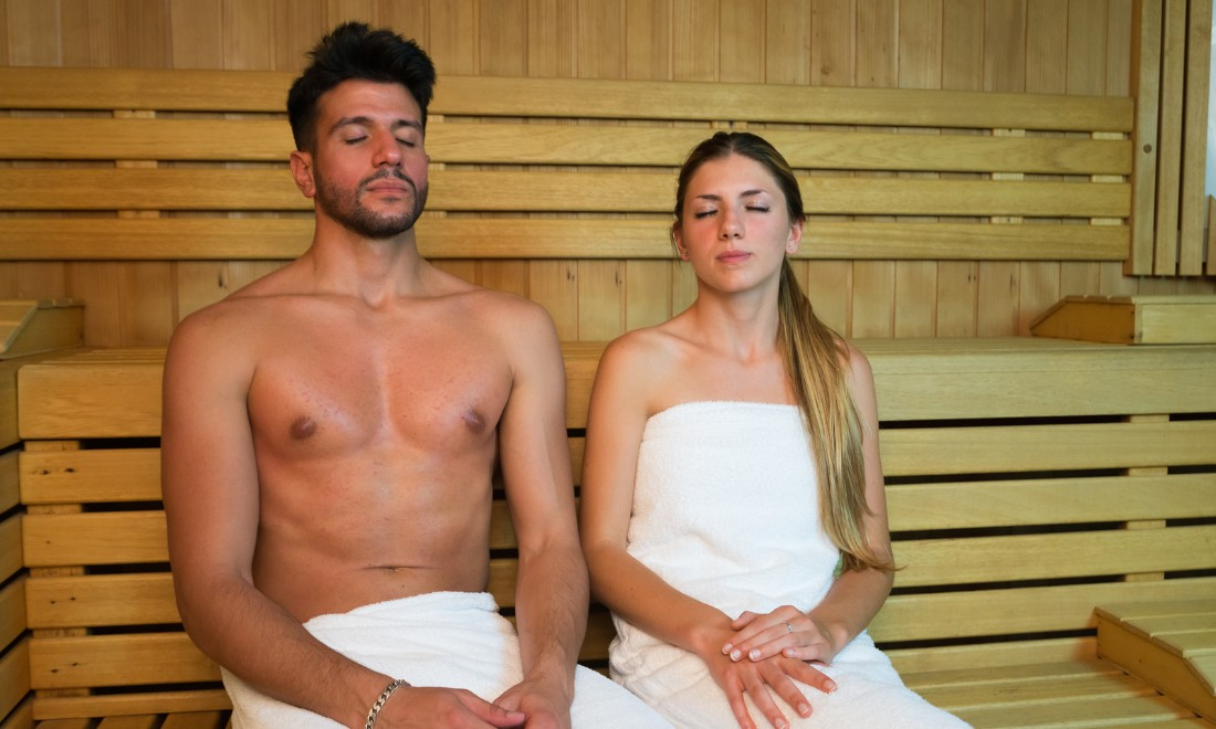 Couple in a sauna in white towels with eyes closed