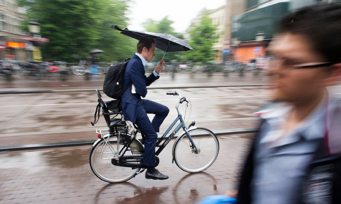 businessman cycling in amsterdam with an umbrella