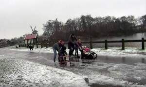 Ice skating and beer crate curling on frozen Dutch roads
